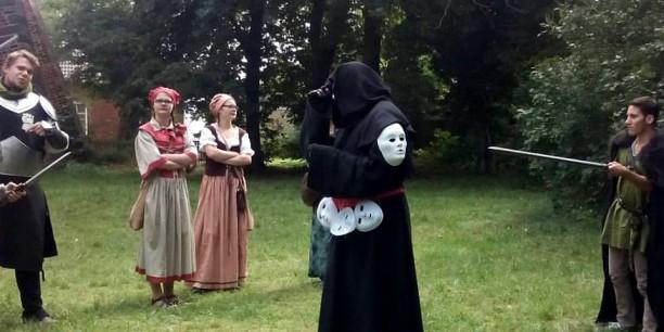 """Wie ist mit Fremdheit umzugehen? Spielende umringen das """"fremde Wesen"""". Foto: (c) Tobias Thiel"""